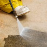 worker powerwashing concrete